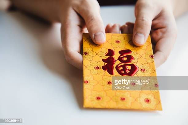 chinese new year celebration-give or receiving red envelop - prosperity stock pictures, royalty-free photos & images