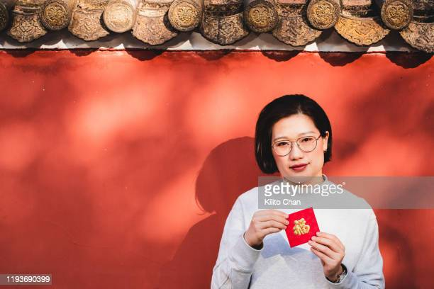 chinese new year celebration-woman giving or receiving red envelop - chinese language stock pictures, royalty-free photos & images