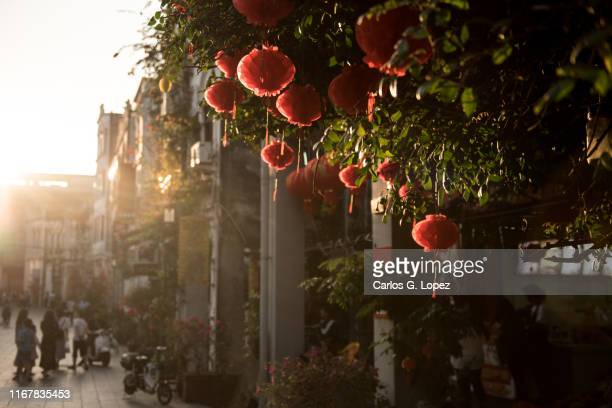chinese new year decoration hanging on beihai's okd street at sunset - golden hour stock pictures, royalty-free photos & images