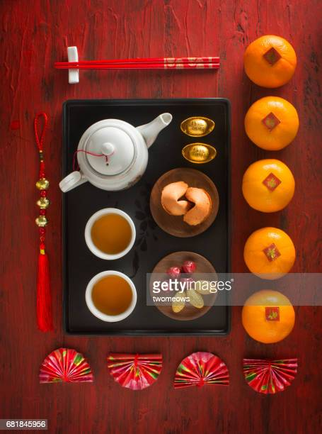 Chinese new year decorative items, food and drinks on red rustic background.