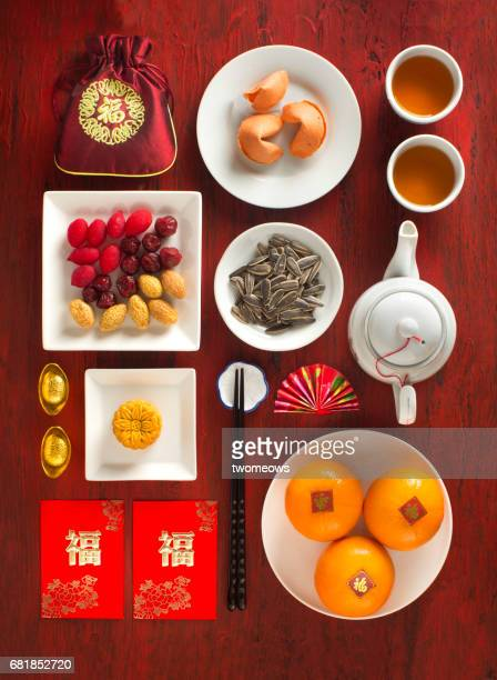 Chinese new year decorative items, food and drinks on rustic red background.