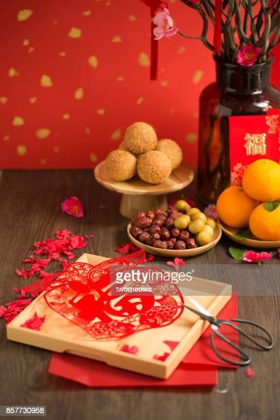 Chinese new year food and decoration items on wooden table top.