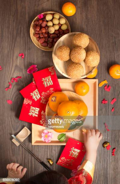 Chinese new year food and decorative items on rustic wooden table top.