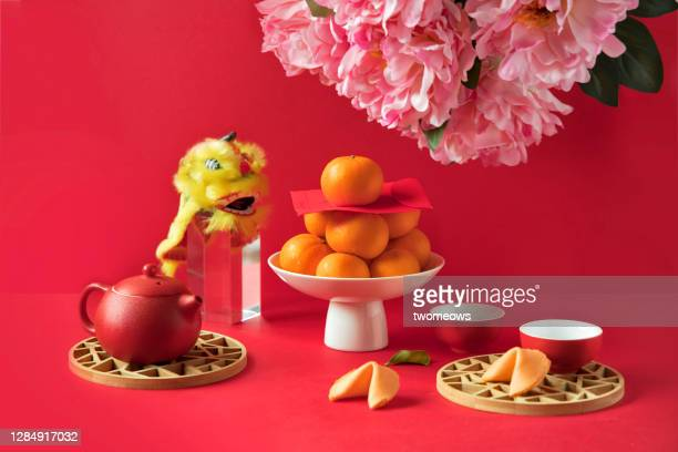 chinese new year food, mandarin oranges and tea set on red background. - chinese new year stock pictures, royalty-free photos & images