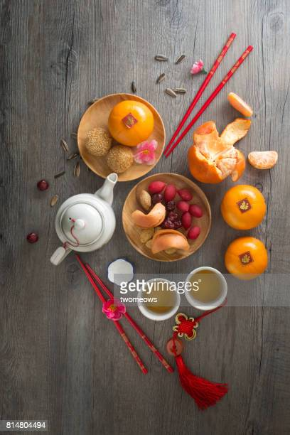Chinese new year food, snack and hot tea served on rustic wooden background.