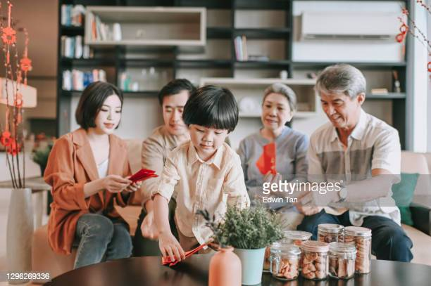 chinese new year multi generation family sitting on sofa living room bonding - ceremony stock pictures, royalty-free photos & images