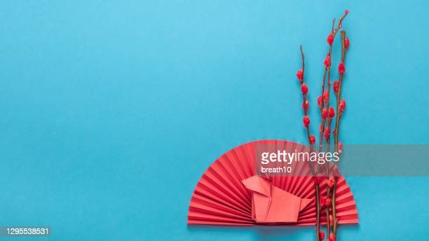 chinese new year ornament. chinese zodiac sign year of ox. red artificial plum blossom, origami paper semicircle and pig symbol of 2021 on blue background, free space for text, minimalism. - chinese new year stock pictures, royalty-free photos & images