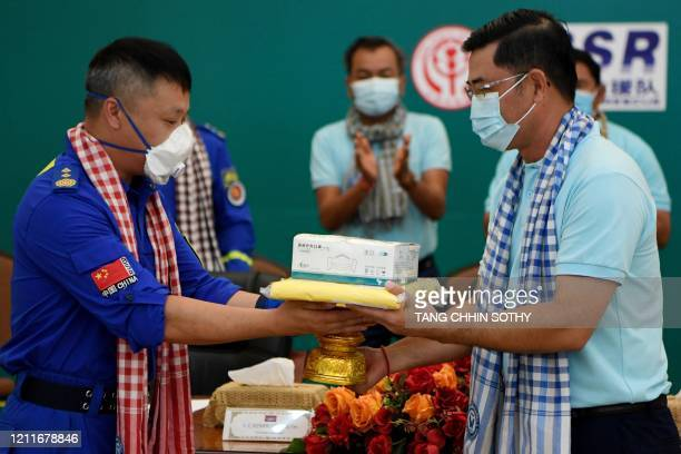 Chinese non-governmental organisation Blue Sky Rescue's Wang Yi presents aid, including medical equipment, to the Cambodian Civil Society Alliance...