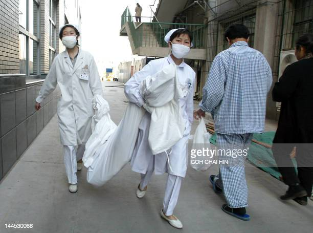 Chinese nurses don surgical masks as they carry out their chores at a hospital in Beijing 07 April 2003 Two more people have died in China from...