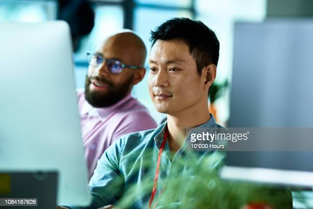 chinese office worker at desktop computer with colleague - looking stock pictures, royalty-free photos & images