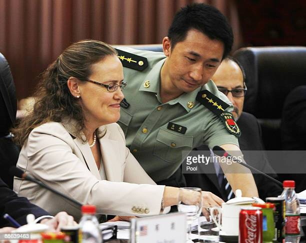 Chinese officer adjusts a microphone for United States Department of Defense Under Secretary Michele Flournoy, at the opening of the U.S. - China...