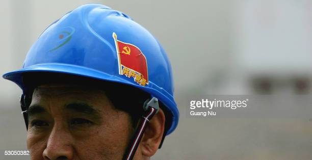 Chinese official wears a helmet with a Chinese Communist Party flag at Qinshan Nuclear Power Plant June 10 2005 in Qinshan of Hangzhou city Zhejiang...