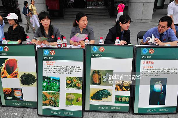 Chinese officials sit behind drug posters on display ahead of the UN's antidrug day in Beijing on June 26 2008 China has executed three convicted...