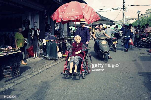 CONTENT] Chinese old couple was walking in street with wife on the wheelchair pushed by husband