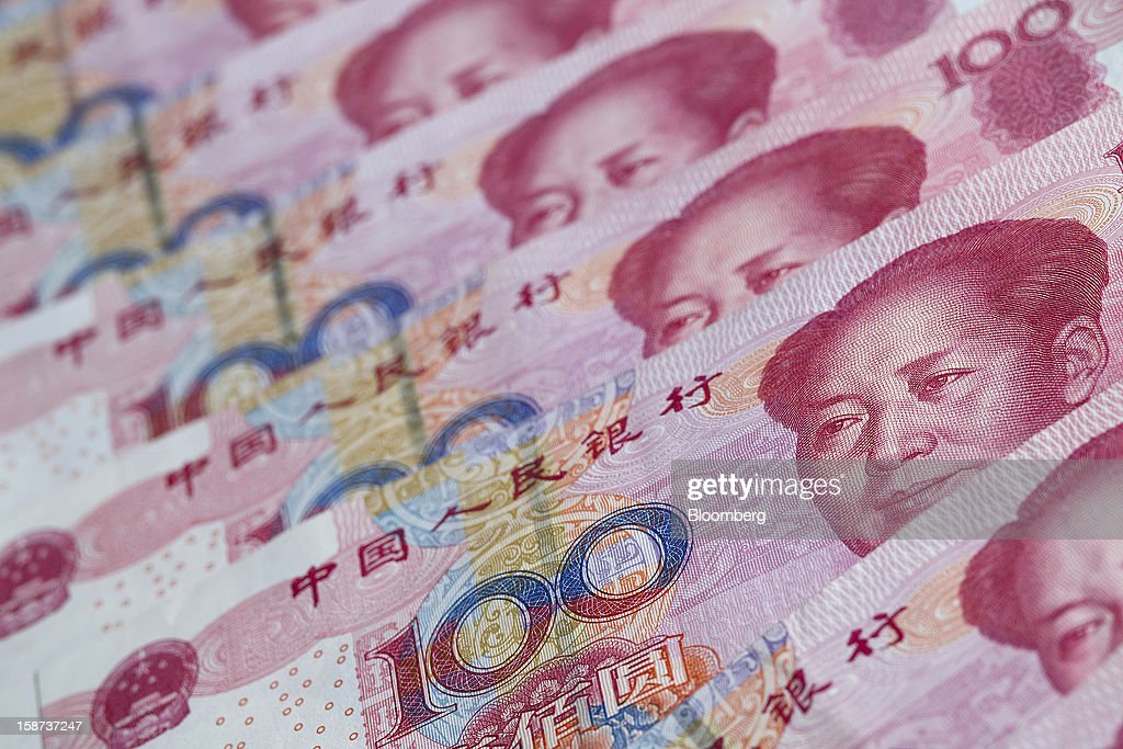 Chinese one-hundred yuan banknotes are arranged for a photograph in Hong Kong, China, on Wednesday, Dec. 26, 2012. China's yuan fell for a fourth day after the central bank set the currency's reference rate at a five-week low amid concern budget deficits in advanced nations will hurt the global economy. Photographer: Jerome Favre/Bloomberg via Getty Images