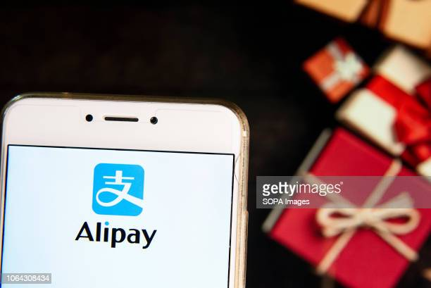 Chinese online payment platform owned by Alibaba Group Alipay logo is seen on an Android mobile device with a Christmas wrapped gifts in the...