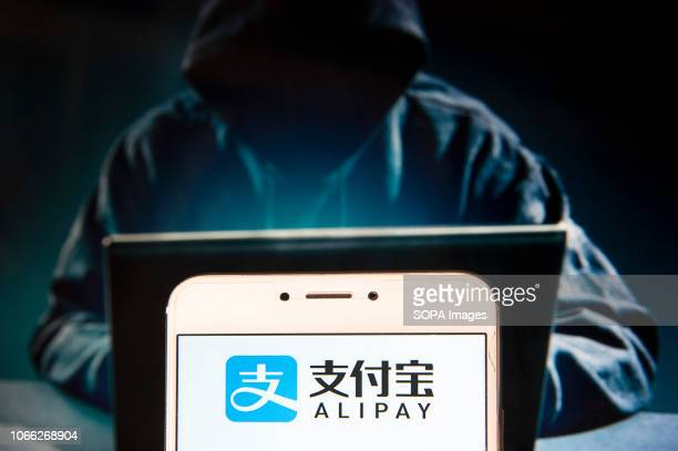 Chinese online payment platform owned by Alibaba Group Alipay logo is seen on an Android mobile device with a figure of hacker in the background