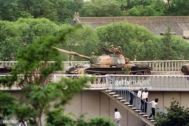 Chinese onlookers run away as a soldier threatens them with a gun on June 5 1989 as tanks took position at Beijing's key intersections next to the...