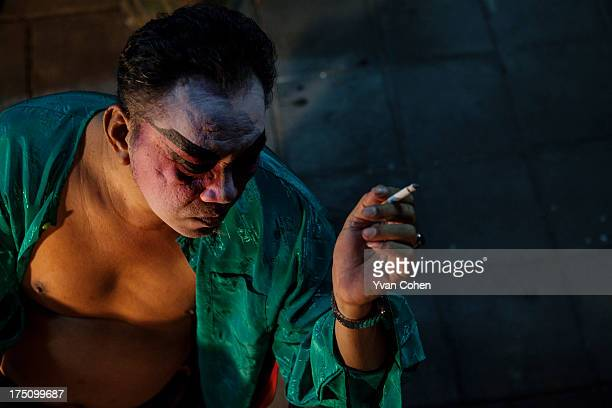 Chinese opera performer enjoys a quick cigarette between scenes during a performance in Bangkok Chinese opera is performed in Thailand by itinerant...