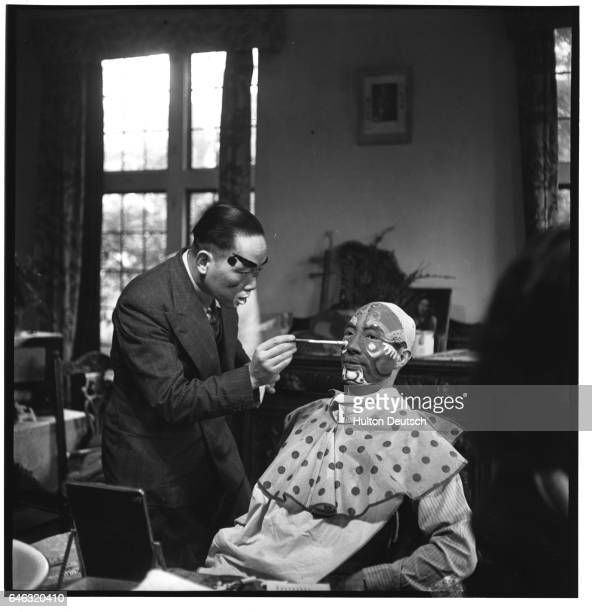 Chinese Opera performer K H Chang applies stage makeup on performer C S Lu for their parts in The Fisherman's Revenge Opera