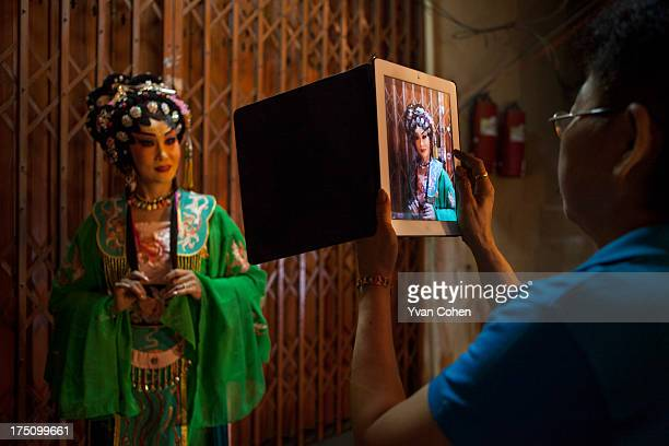 Chinese Opera performer poses for a fan who is photographing here with an Ipad Chinese opera is performed in Thailand by itinerant groups of players...