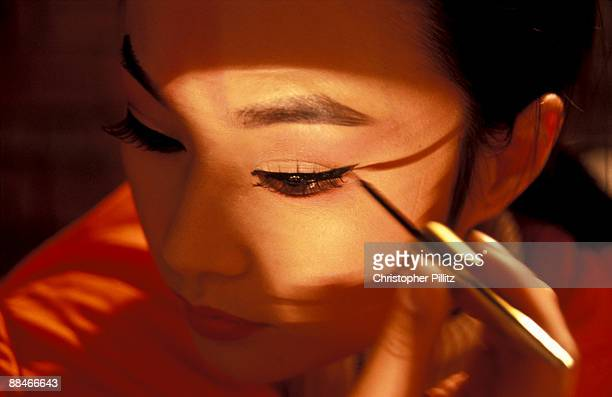 Chinese opera singer applies make up to face