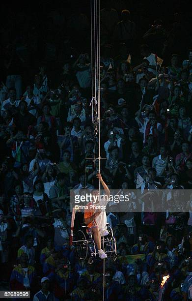 Chinese Paralympic athlete Hou Bin draws himself to the main torch during the Opening Ceremony for the 2008 Paralympic Games at the National Stadium...