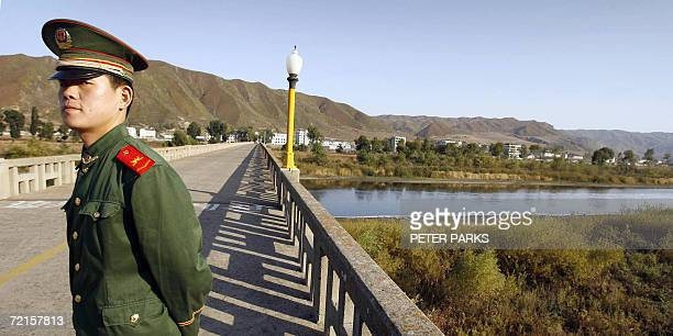 Chinese paramilitary border guard patrols a bridge leading to North Korean on the Chinese/North Korean border in the town of Tu Men in China's...