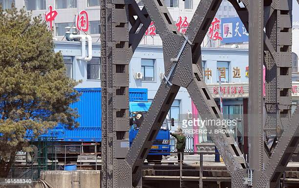 A Chinese paramilitary border guard reaches to check for proper documentation from drivers as trucks cross the SinoKorean Friendship Bridge...