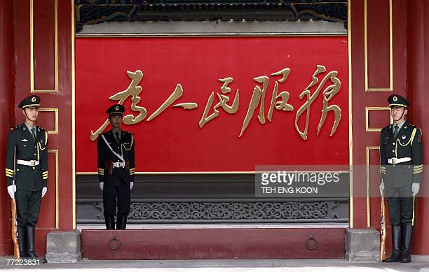 Chinese paramilitary guards stand at the front of a slogan reading 'Serve the People' displayed at the Zhongnanhai communist leaders compound in...