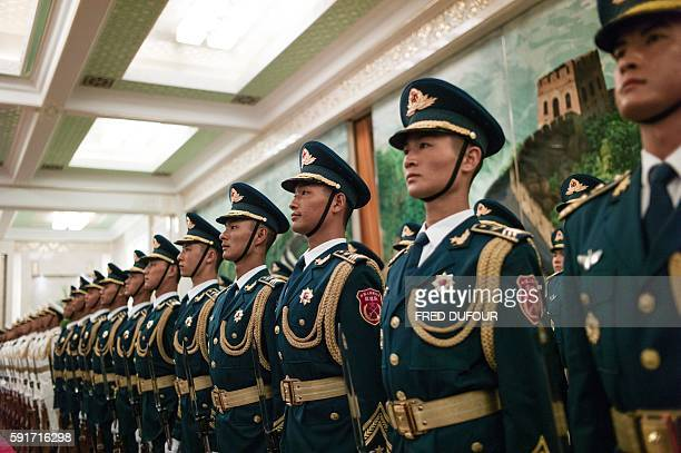 TOPSHOT Chinese paramilitary guards stand during a review military honour guard by Myanmar State Counsellor Aung San Suu Kyi and Chinese Premier Li...