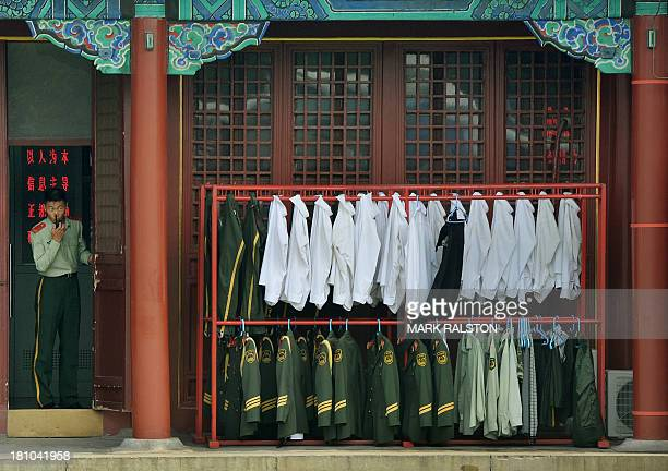 A Chinese paramilitary officer talks on a walkietalkie outside his barracks in Beijing on September 19 2013 Fallen Chinese politician Bo Xilai has...