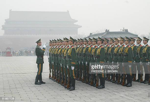 Chinese paramilitary officers are lectured during afternoon drills at the Forbidden City as a haze of smog hovers over Beijing, 14 December 2004....