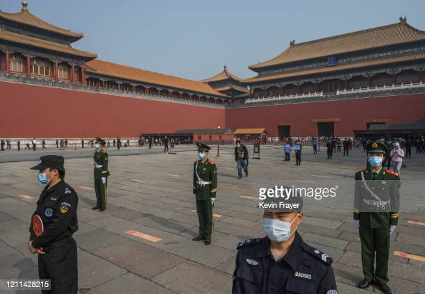 Chinese paramilitary police and guards practice social distancing as they wear protective masks while standing in front of the entrance to the...