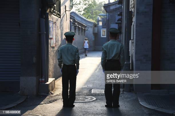 Chinese paramilitary police guard an alley in a street next to Tiananmen Square ahead of an overnight rehearsal of a military parade to mark...