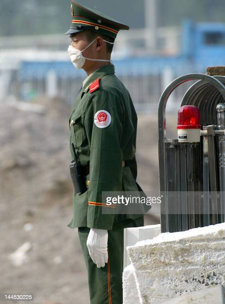 A Chinese paramilitary police guards the entrance to the hospital erected in barely a week to house a rapidly increasing number of Chinese patients...