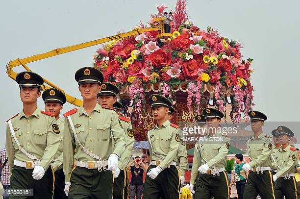 Chinese para-military police march as workmen put the finishing touches on a giant flower pot in Tiananmen Square as the city prepares for the...