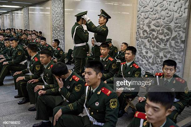 A Chinese paramilitary police officer adjusts another's cap as they and others wait in an underground tunnel before securing the official flag...