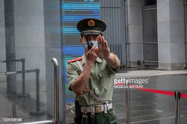A Chinese paramilitary police officer gestures and speaks over his twoway radio whlie standing at the entrance gate of the Australian embassy in...