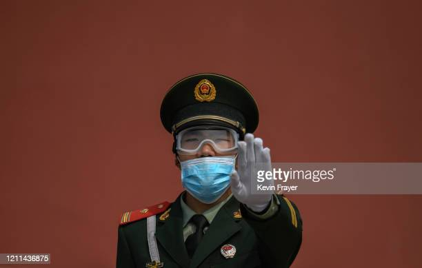 Chinese paramilitary police officer gestures as he wears a protective mask while standing guard at the entrance to the Forbidden City as it reopened...