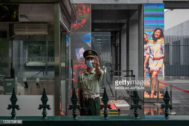 A Chinese paramilitary police officer gestures while standing at the entrance gate of the Australian embassy in Beijing on July 9 2020 Australia on...