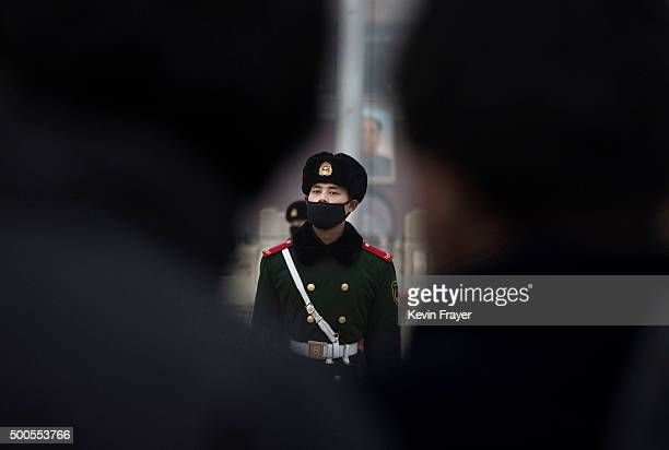 Chinese Paramilitary police officer wears a mask to protect against pollution, a rare occurence, as they march during smog in Tiananmen Square on...