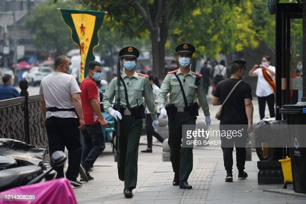 Chinese paramilitary police officers patrol in a street south of Beijing's Tiananmen Square ahead of the opening ceremony of the Chinese People's...