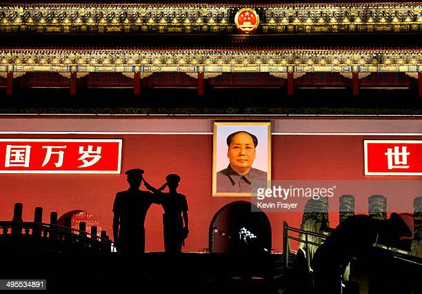 Chinese Paramilitary police officers salute each other as they stand guard below a portrait of the late leader Mao Zedong in Tiananmen Square on June...