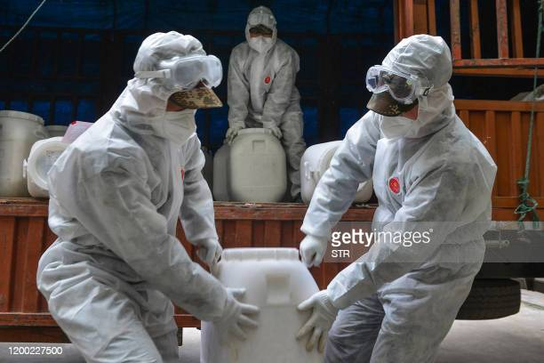 Chinese paramilitary police officers wearing protective gears transfer pails of disinfectant in Yunmeng county outside Xiaogan City in China's...