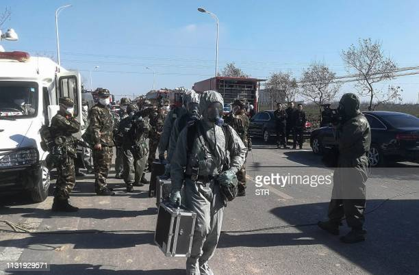 TOPSHOT Chinese paramilitary police officers wearing protective suits make their way to the site of an explosion as they prepare to measure the...