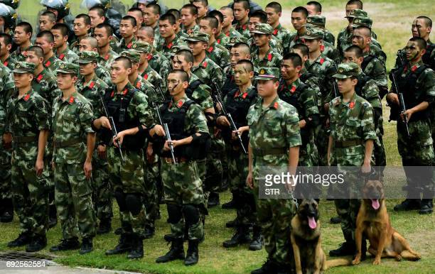 Chinese paramilitary police officers who serve on the border between Hong Kong and Guangdong province prepare to take part in anti-riot training...