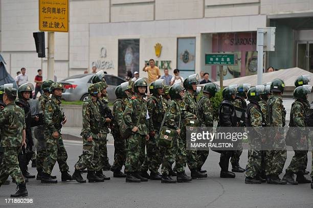 Chinese paramilitary police prepare to ride in armoured vehicles during a 'show of force' ceremony in Urumqi after a series of terrorist attacks...