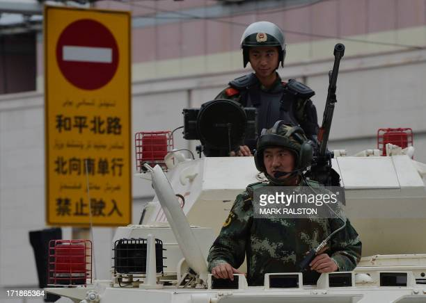Chinese paramilitary police ride in armoured vehicles during a 'show of force' ceremony in Urumqi after a series of terrorist attacks recently hit...