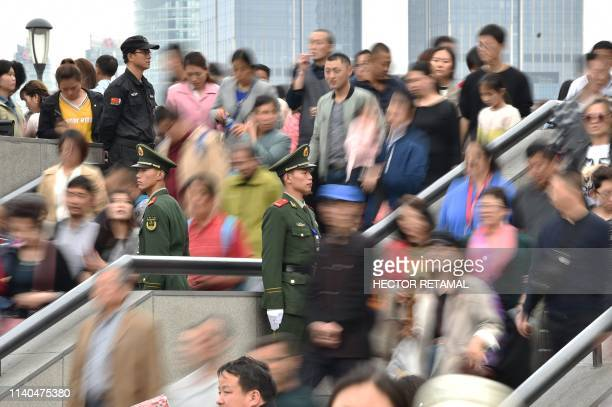 Chinese paramilitary police stand guard while people visit the promenade on the Bund along the Huangpu River during a May Day holiday in Shanghai on...